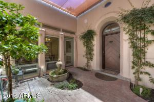 Custom Shaded Awning over Remarkable Cobblestone Garden Courtyard with Soothing Water Feature and Several Doorways Creating Usable Living Space