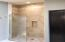 "Travertine shower with glass panel and a brushed marble ""drying area"""