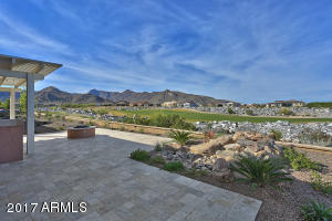 Professionally landscaped yard with extended travertine patio