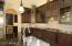 Kitchen open to Butler pantry with wine refrigerator.