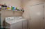 Laundry room with shelving space. Opens to 2 car garage.