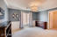 Wainscotting and crown molding highlight this spacious bedroom