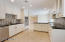 The spacious kitchen boasts dark granite counter tops, new white cabinets and stainless steel appliances.