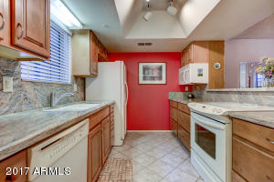 Galley style kitchen with updated flooring, cabinets and granite counters