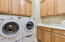 Laundry room with plenty of cabinets and utility sink.