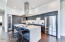 Kitchen with quartz counters, stainless suite and wine fridge