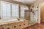 large soaking tub and shower with glass enclosure.