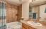Guest bathroom has decorative tile tub/shower