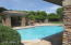 View part of back yard and long covered patio and pool from garden