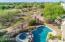 The backyard is surrounded by lush desert vegetation.