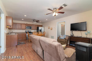 Open floor plan with ceiling fans, wood laminate flooring & 2-tone paint.