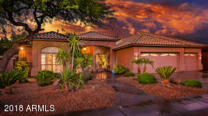 Spectacular sunrise sky over, impeccable custom designed home, professional designed landscaping with mature trees with the look of art sculpture.
