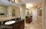 LUXURIOUS MASTER BATH BOASTING HIS & HERS VANITIES AND WALKIN CLOSETS, CUSTOM TILED WALKIN SHOWER WITH DUAL SHOWER HEADS, ROMAN TUB