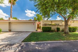 Lovely landscaped front with large shade tree.