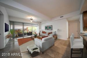 Virtually staging shows spacious living room open to kitchen bar & outdoor patio