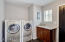 Laundry room features side-by-side front loading washer/dryer, cabinet with granite counter & door to yard.