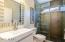 Guest Bath off front entry with floating vanity and glass tile shower