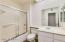 Brightly lit guest bathroom is set off from main living space