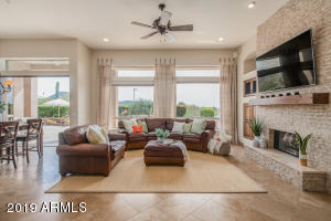 Open concept living room, eat-in dining and kitchen, gas fireplace, automatic sliding door and stunning mountain, city light and sunset views