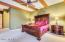 Soaring ceiling, separate exit to backyard from master bedroom, bay windows with blinds & drapes, custom wood beams, ceiling fan, built in shelving, two tone paint, carpet