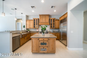 A true chef's kitchen with subzero appliances, Wolf built in oven, warmer, gas cooktop, stainless steel farmhouse sink, over sized island and breakfast bar.