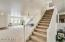 Staircase divides the formal living and dining areas from the great room with kitchen, informal dining and family room.