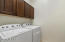 laundry room has cabinets above the included washer & dryer. Cabinet an sink is on the other side.