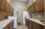 Oversized laundry with LG side-by-side washer and dryer, laundry sink, laminate countertops, extensive cabinetry with rollouts, and a Frigidaire fridge/freezer.
