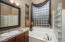 His and her separate vanities with tile countertops, medicine cabinets, and cherry wood cabinetry with oil rubbed bronze hardware. Soaking tub with water jets and a glass block walk-in shower.