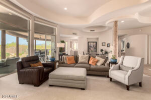 Bright and open living room with large windows viewing large covered patio.
