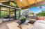 Covered veranda with panoramic sliding door leads to kitchen & great room