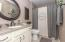 • Ceramic tile flooring • Tan painted walls • Enclosed vanity with single bowl, cultured marble sinktop • 2 bulb wall light • Round mirror remains • Tub/shower combination • Ceiling exhaust