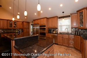 Stunning oversized kitchen- double wall oven, SS appliances, travertine floor, glass tile backsplash, granite, 2 separate sink areas, pantry, gas stove