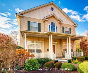 Classic colonial with CertainTeed Carriage House roof shingles. So pretty with a rocking chair front porch.