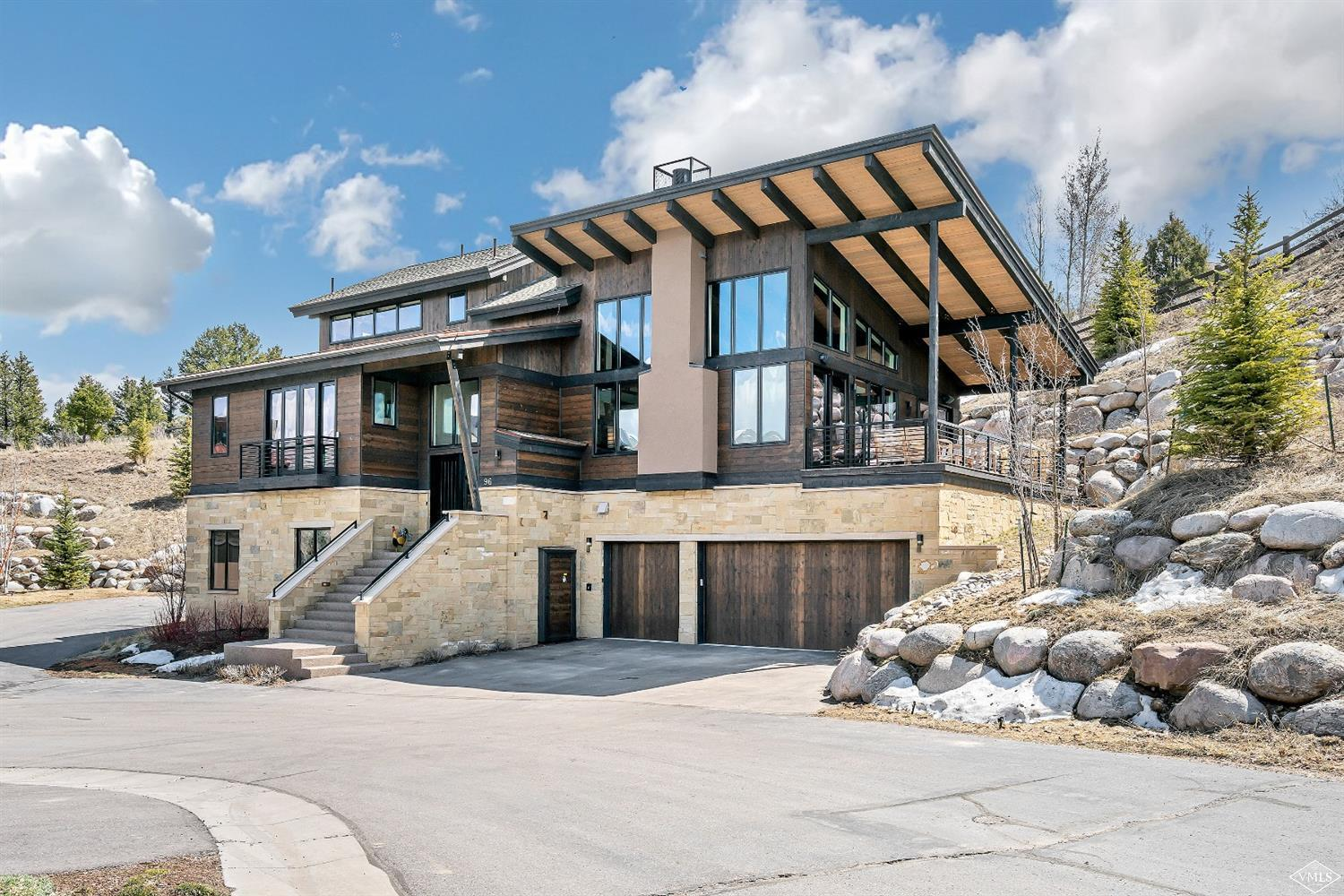 Mountain contemporary green-built home in quiet location offers all day sunshine through massive windows with panoramic western and northern views. Gourmet kitchen with high-end appliances opens into vaulted great room with exposed beams, dry stacked fireplace and expansive Ipe deck. Complete with 3-car garage, 2-master suites one on main level, office, family room with wet bar and wine room.