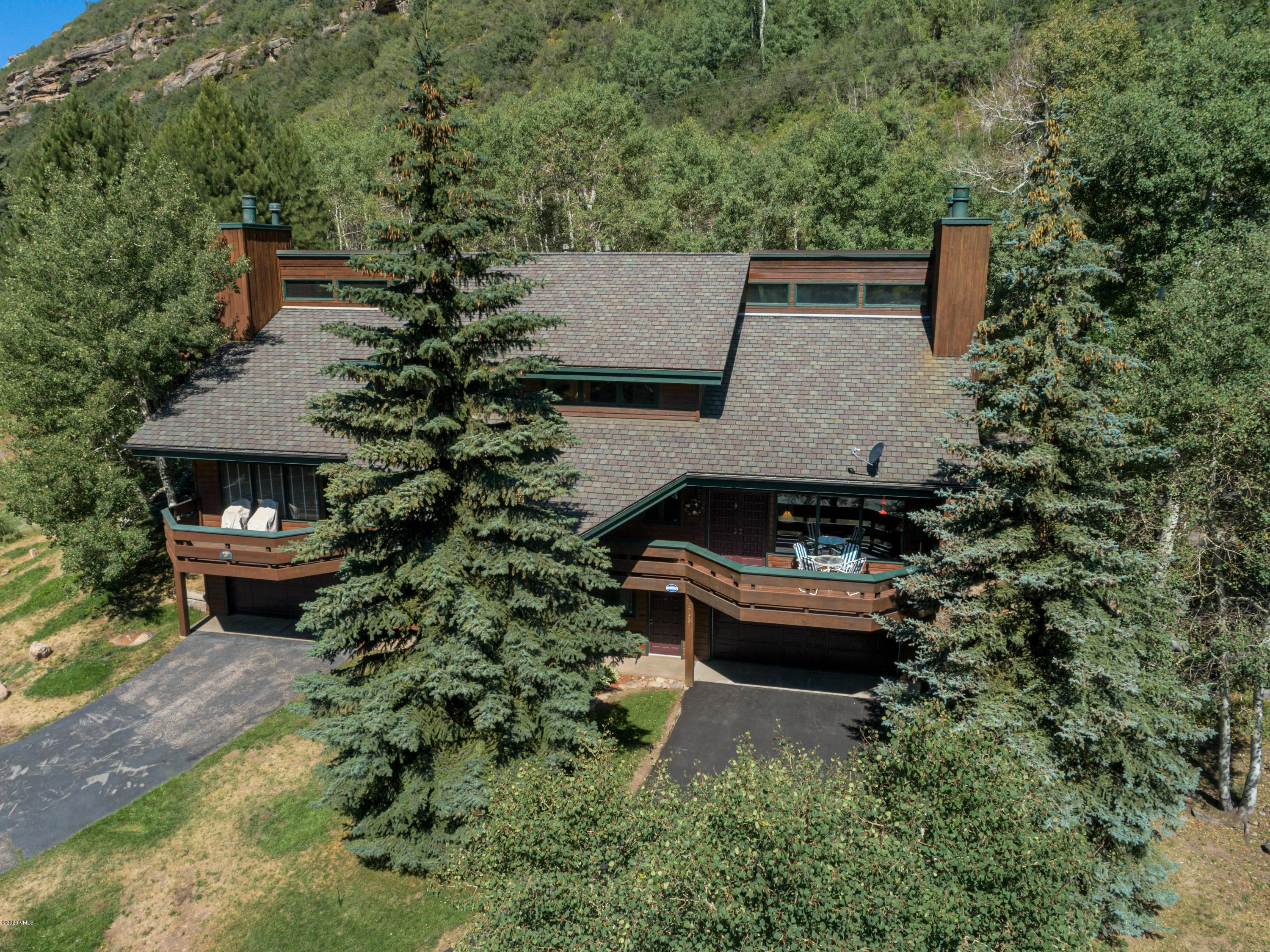 Located on a quiet street in the Booth Creek neighborhood of East Vail, this private, hillside duplex bordering public lands has 4 bedrooms, 3 1/2 baths and a 2-car garage. This exceptionally maintained home is landscaped with stunning alpine gardens and a patio in the backyard for enjoying the mountain scenery. The beautifully renovated large kitchen has uplighting above the cabinets; downlighting onto the granite countertops; a breakfast island that seats two chairs as well as a dry bar with a granite countertop and backsplash, wine cooler and glass cabinet. You are sure to enjoy the views of the alpine gardens from the kitchen and dining area.  The comfortable living area has vaulted wood ceilings and a wood burning fireplace with moss rock surround and custom-made glass doors. The numerous windows offer sunlight and beautiful views of the surrounding mountains. The front deck is accessed from the living area and is a perfect place to unwind and enjoy the mountain views. As well, you will find a bedroom and powder room on the main level. The master bedroom and bath are located on the third level along with two bedrooms that are connected by a 3/4 ''Jack 'n Jill'' bathroom with two vanities. The master bedroom has vaulted wood ceilings, a walk-in closet with custom built-ins and views of the alpine gardens and surrounding hillside. The master bathroom has a double vanity with rough edge granite countertops, in-floor heating and also overlooks the backyard hillside and alpine gardens. The lower level houses the 2-car garage, a large laundry room with sink, a separate utility with work bench area, a dry sauna, a 3/4 bathroom and a large mud room with a built-in boot and glove dryer. Outside there is a beautiful stone walkway winding its way through the alpine gardens going up to the private back patio, making for quiet morning coffees and conversation. The roof was recently replaced with Grand Manor, slate-like shingles and the driveway was recently redone.