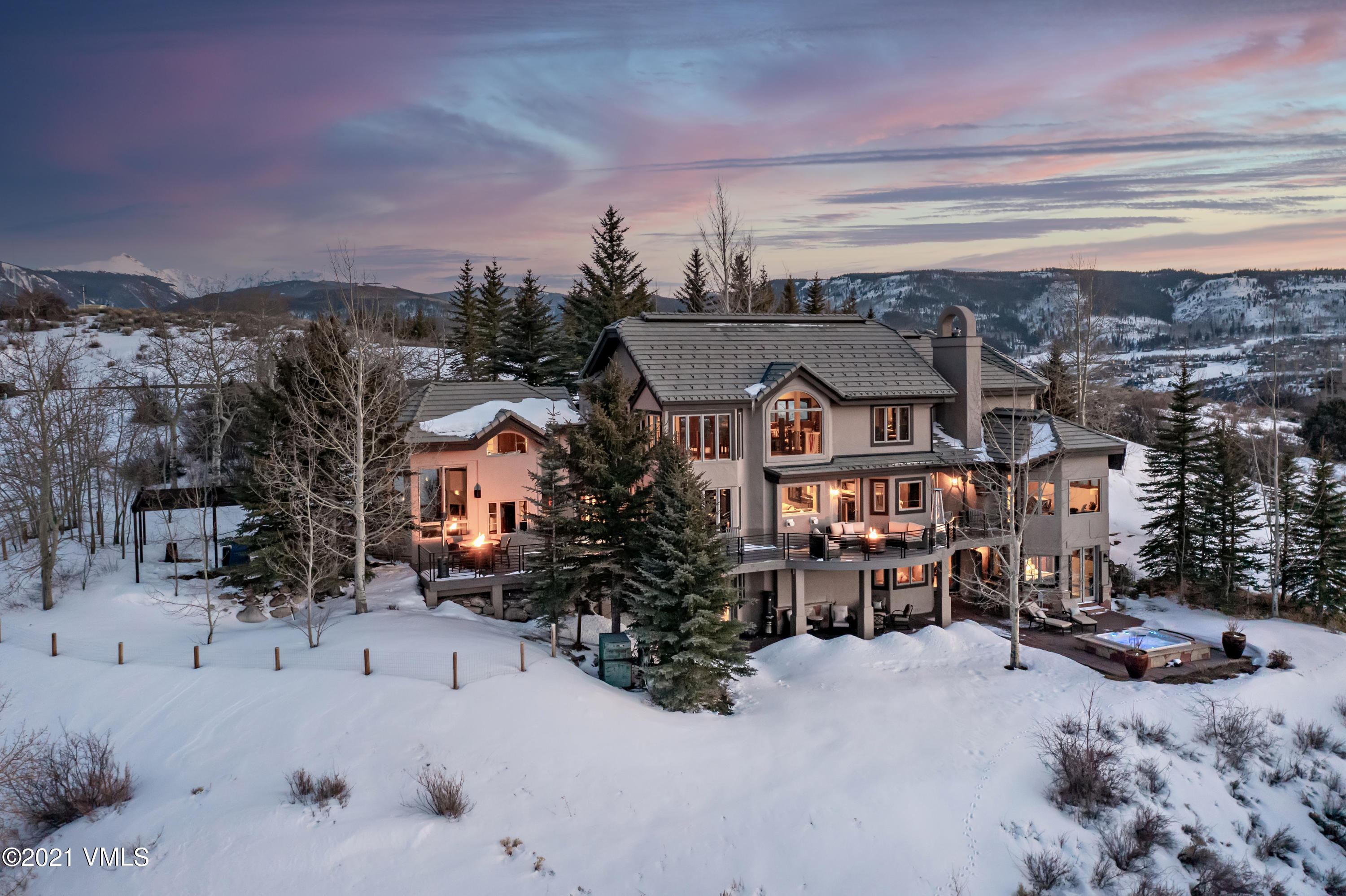 Situated atop Casteel Ridge at the end of a private cul-de-sac, this stunning residence captures truly awe inspiring views of the Vail Valley.  Guests will walk in the front door and immediately be mesmerized by the stunning views.  Walk them down the grand staircase that connects the upper level billiard and game area to the living room, dining area, bar and kitchen.   What an oasis after a day of exploring the ski mountains.  Relax in the outdoor saltwater hot tub on the lower patio or cozy up around the gas firepit on the upper wraparound deck with unspoiled views as far as the eye can see.  Complete the evening on a cinematic adventure in the media room downstairs, housing a 70'' movie theatre-style flat screen HD TV with surround sound. The property is privately situated on over 2 acres and has an expansive backyard that is great for all to enjoy.  Parents can hang out on the enormous new deck enjoying a glass of wine while overlooking the nice flat grass yard below where the kids can throw a ball for the dogs.  Enjoy the extraordinary meandering gardens that wrap around the home creating gorgeous flowers that bloom from April through October.  This stylish and scenic mountain residence has been renovated and interior designed in a mountain modern aesthetic to create a captivating and comforting setting.  The main level features a custom-built quartz double fireplace in the living room, an expansive great room with soaring cathedral ceilings and both formal and informal entertainment and dining spaces.  This home has a defiant fun factor but can also be a serene space when friends and family are not in residence.  Enjoy a game of billiards or get creative with craft cocktails while friends are ponied up to the full size bar.  The bar is on the main level next to the kitchen and living room so that it is frequently utilized versus being down in the family room and rarely used.  The media room is the perfect nook to take..  mls.CordilleraDivideLuxury. ..in a grea