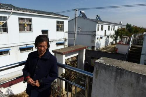 A woman stands among apartments built for villagers relocated to make way for the expansion of the Danjiangkou reservoir, at Lia