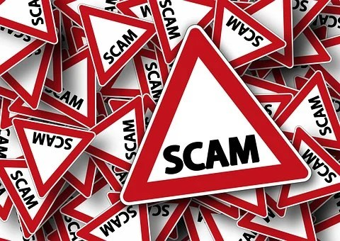 Triangular traffic sings with red borders and whte background with the inscription SCAM