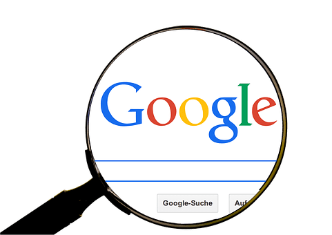 Search engine symbolized by a magnifying glass with the words Google and the search window showing through.