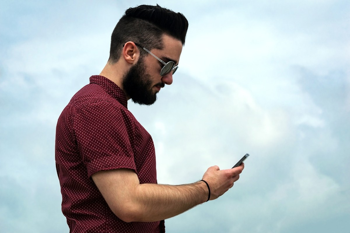 A man smiling as he looks at his smartphone