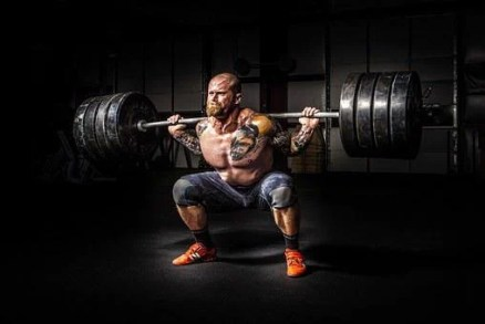 A hefty man lifting a heavy weight