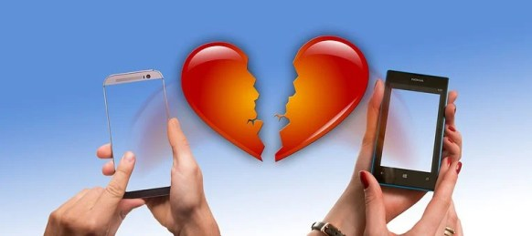 Two hands texting on both sides of a broken heart