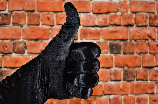 A hand in black gloves with a thumb up to show greatness.