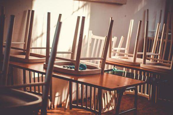 summer classroom. chairs on desks except for one