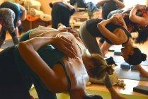 Groupe d'adultes faisant du yoga