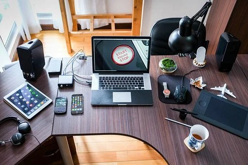 A desk filled with accessories such as laptop, iphone, etc to signify professional
