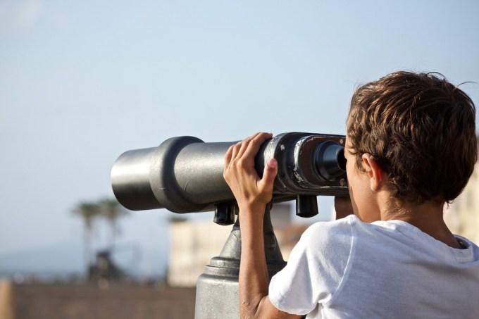 Une personne observe le ciel à travers un téléscope