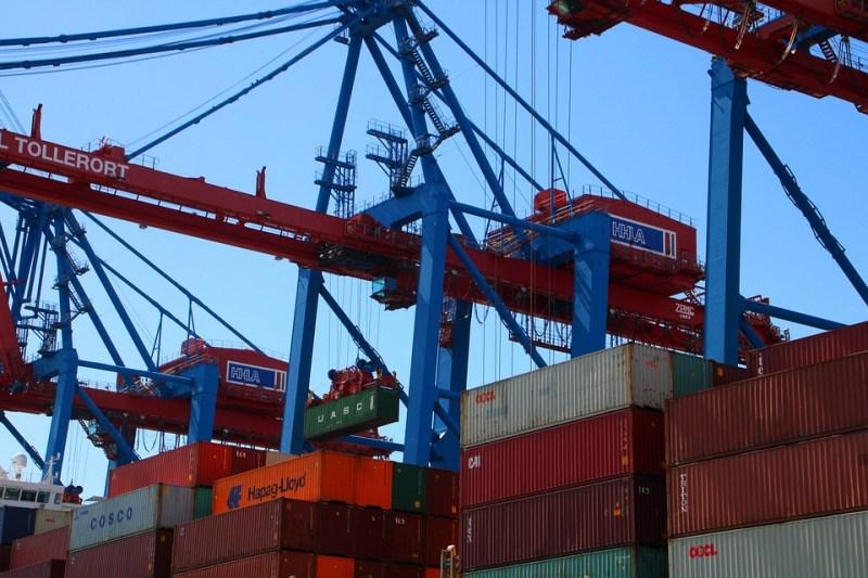Na imagem containers em um porto. | Texto: Descubra o que são e como investir em commodities - Positive Company