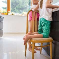 Little Girl Chairs Electric Recliner Chair Covers Australia Kneeling On A Next To Her Mom Helping With Food Preparation Stock Photo Pixeltote